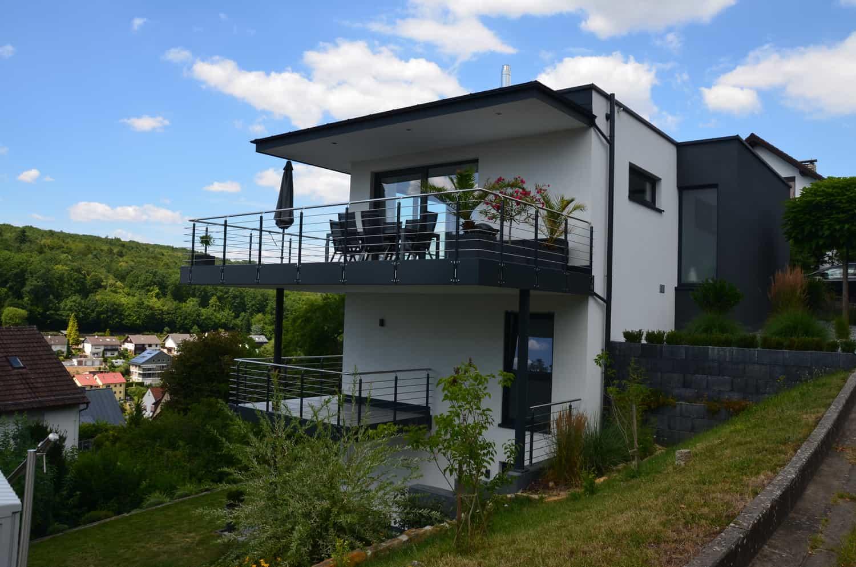 Zweigeschossiges Haus mit Teilunterkellerung, Anbau und Flachdach. 2 Balkone in Mainberg
